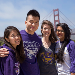 Students in purple SF State gear at the Golden Gate Bridge