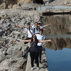 International students balance between rocks and water at Sutro Baths